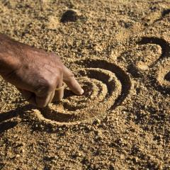 man drawing dreamtime story in sand